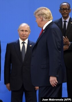 Президент США Дональд Трамп проходить повз президента Росії Володимира Путіна, коли учасники саміту «Групи двадцяти» готувалися до колективної фотографії. Аргентина, Буенос-Айресі, 30 листопада 2018 року