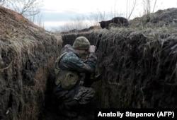 Кот смотрит на украинского солдата, отдыхающего в окопе на линии фронта с поддерживаемыми Россией сепаратистами недалеко от села Красногоровка.