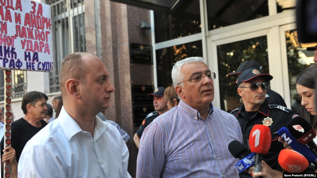 Montenegrin oppositionists Andrija Mandic (right) and Milan Knezevic meet with supporters as they arrive for a court hearing in Podgorica on July 20.