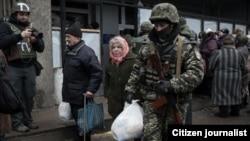 Раздача гуманитарной помощи в Дебальцево, начало февраля 2015 года. Военный помогает нести пакет пожилой женщине. К концу месяца город попал под оккупацию и остается захваченным доныне