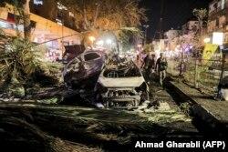 Силы безопасности Израиля проходят мимо сгоревших автомобилей в Холоне недалеко от Тель-Авива 11 мая 2021 года после того, как члены ХАМАС выпустили в направлении Израиля несколько ракет.