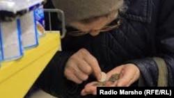 Літня жінка рахує гроші в продуктовому магазині, ілюстративне фото