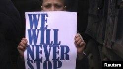 """Молодой сириец с плакатом """"Мы не остановимся, пока не победим"""". Хомс, март 2012 года."""