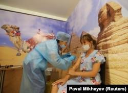 Женщина получает дозу вакцины «Спутник V» во временном пункте вакцинации, созданном в бывшей студии TikTok в торговом центре MEGA Park в Алматы, Казахстан, 23 июня 2021 года