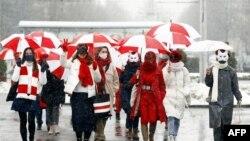 Жінки в карнавальних масках йдуть вулицями під парасольками кольорів біло-червоно-білого прапора Білорусі на знак протесту проти результатів виборів президента Білорусі в Мінську, 26 січня 2021 року