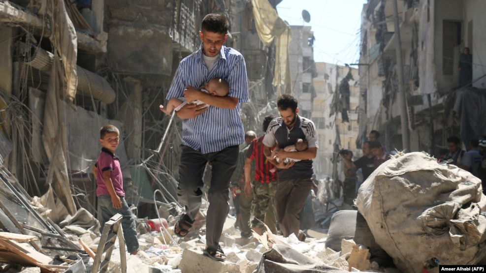 Syrian men carrying babies make their way through the rubble of destroyed buildings following a reported air strike on a rebel held neighborhood of the city earlier this year.