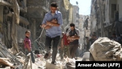 Bărbații sirieni care-și croiesc drum printre dărâmături, cu bebeluși salvați în urma unui atac aerian asupra cartierului Salihin din orașul Alep, în septembrie 2016