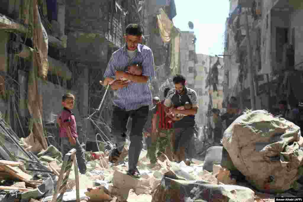 Сирийские мужчины с младенцами на руках пробираются через завалы разрушенных зданий после сообщения об авиаударе по удерживаемому повстанцами району Салихин города Алеппо. 11 сентября 2016 года (AFP/Ameer Alhabi).