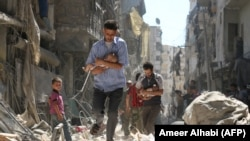 Чоловіки несуть на руках немовлят розгромленим війною містом Алеппо на півночі Сирії, 11 вересня 2016 року