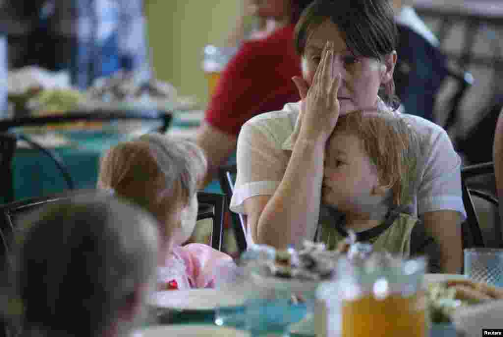 Families who have fled fighting in Slovyansk eat at the canteen of the Makiyivsky Coke and Chemical Plant in the town of Makiyivka on June 4.
