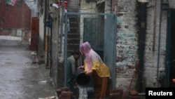 A man helps his wife to remove water from their home which flooded due to heavy rain in Lahore September 5, 2014.