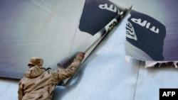 """Ирак аскери """"Ислам мамлекети"""" радикал уюмунун туусун дубалдан алып атат."""