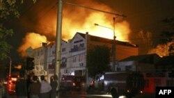 Люди смотрят на горящее здание в Махачкале. Пожар начался в результате боя между милицией и несколькими вооруженными местными жителями (21 сентября 2007 года)