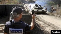 A member of the OSCE monitors the withdrawal of tanks of the Ukrainian armed forces near the village of Nyzhnje in the Luhansk region on October 5.