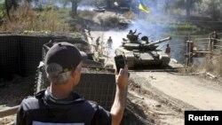 Представник ОБСЄ спостерігає за відведенням українських танків у рамках домовленостей про відведення від лінії зіткнення озброєння калібром до 100 мм. Селище Нижнє, Луганська область, 5 жовтня 2015 року