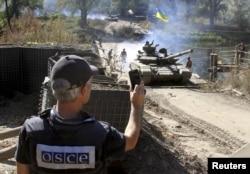 Один из членов миссии ОБСЕ наблюдает за отводом украинской бронетехники у линии соприкосновения сторон в Луганской области
