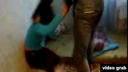 "Screengrab from a video showing a Kyrgyz woman, ""Ajna,"" being beaten, purportedly for associating with non-Kyrgyz men"