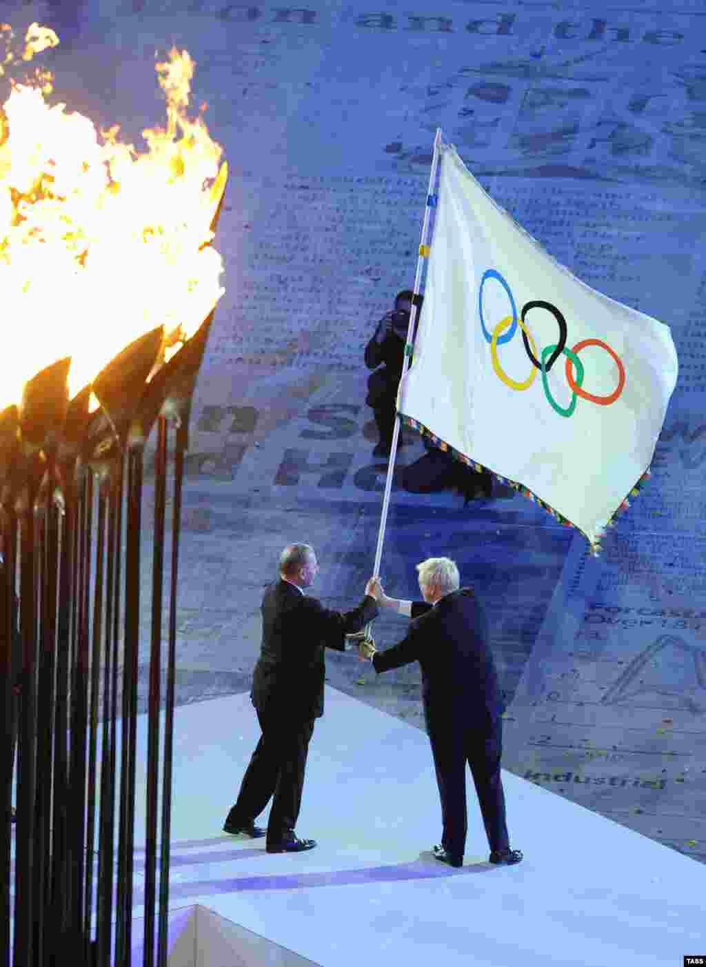 Олимпия комитеты рәисе Жак Рогге һәм Рио-де-Жанейро мэры Эдуардо Паес (с) ябылу тантанасында Олимпия әләмен күтәрә