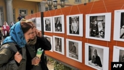 Afghanistan - Two Afghan teachers look at photographs from the 'Tales from a Globalizing World' photo exhibition at the Ayesha Durani High School in Kabul, 08Apr2008