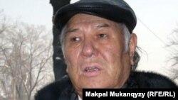 Писатель Дулат Исабеков перед зданием банка. 8 февраля 2012 года
