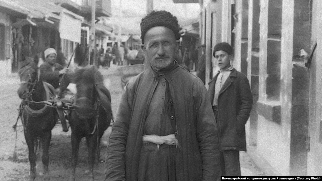 Bakhchysaray, 1920s. Men covered their heads with a low cap made of sheep leather, a skullcap, or fez hat. A shirt with wide sleeves was tucked into wide cloth harem pants and was belted with a wide sash. A short vest with buttons was put on top of the shirt, and a long caftan on top of it.