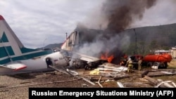 Firefighters work on extinguishing a fire on an An-24 passenger plane at Nizhneangarsk airport on June 27.