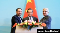 FILE: (L to R) Afghan Foreign Minister Salahuddin Rabbani with his Chinese counterpart Wang Yi and Pakistani Foreign Minister Khawaja Asif in Beijing in December 2017.