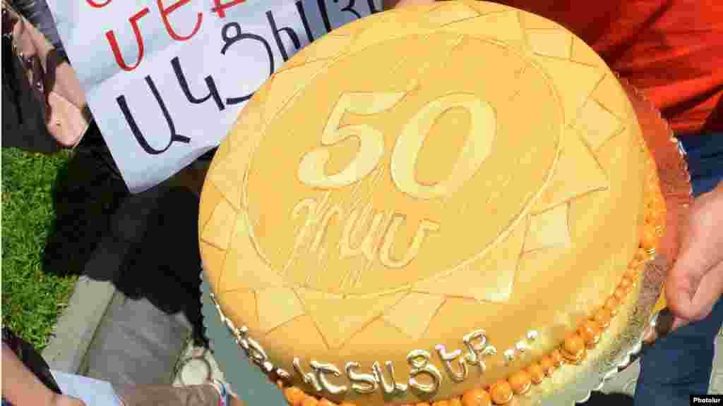 """Aksiyaçılar özləriylə merə çatdırılmaq üçün tort da gətiriblər. Tortun üstündə belə yazılıb: """"50 dram, yeyin, zəhəriniz olsun"""". Amma polis aksiyaçılara meriya binasına daxil olmağa imkan verməyib."""