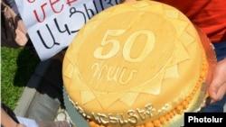 """Aksiyaçılar özləriylə merə çatdırılmaq üçün tort da gətiriblər. Tortun üstündə belə yazılıb: """"50 dram, yeyin, zəhəriniz olsun"""". 25 iyul 2013"""