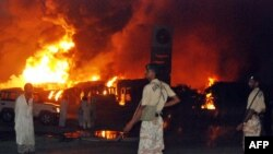 Pakistani paramilitary soldiers stand guard as trucks and tankers carrying supplies bound for NATO forces in Afghanistan burn following the overnight attack in Shikarpur.