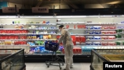 A shopper pushes a cart inside a supermarket on February 11 following an outbreak of the new coronavirus in the Chinese city of Wuhan in Hubei Province.