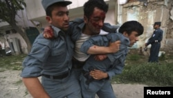 Afghanistan - A wounded Afghan policeman is being carried away from the site of an explosion in Kabul, 24May2013