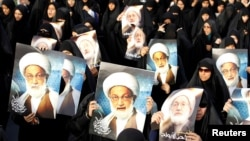 Bahraini protesters hold up posters of Shi'ite cleric Ayatollah Isa Qassem during an antigovernment demonstration in 2013.