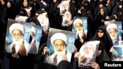 تصاویر عیسی قاسم در دست هواداران بحرینیاش.