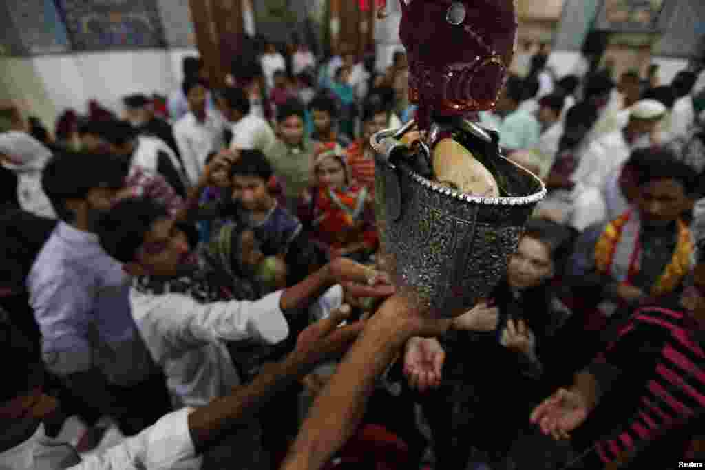 Devotees reach out for sacred water inside the shrine in 2013. Sufism draws on some rituals of pre-Islamic traditions.