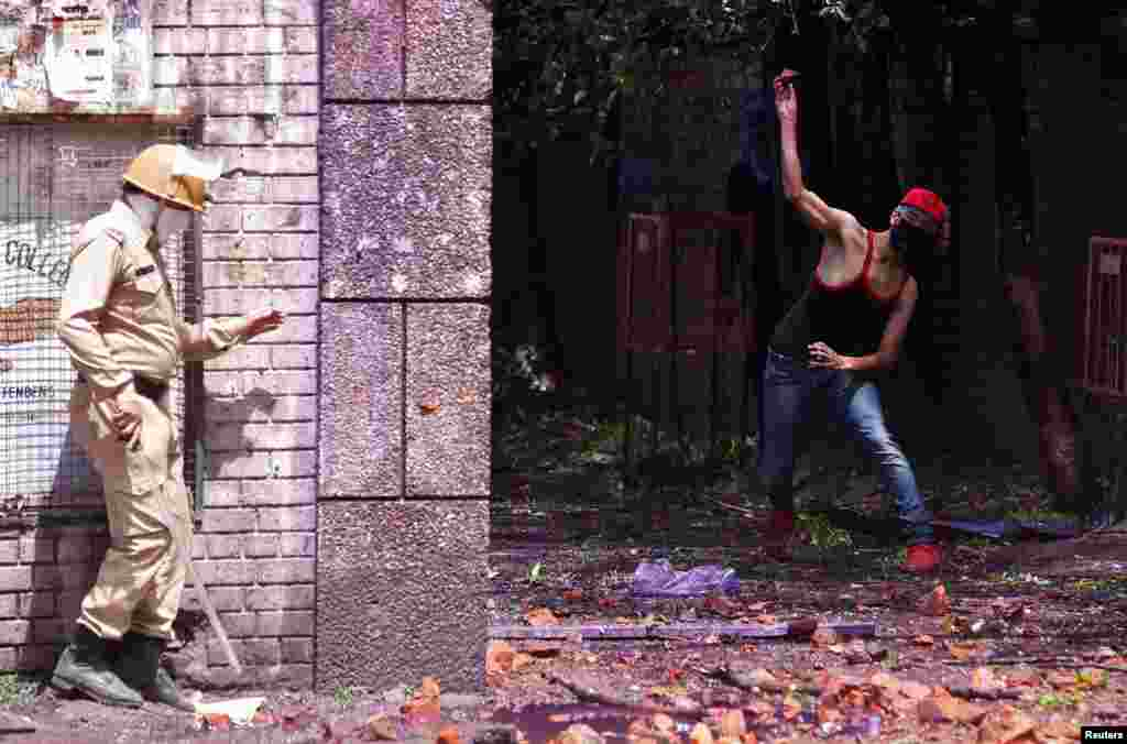 ინდოეთის ქაშმირში, ქალაქ სრინაგარში, სტუდენტი ქვას ესვრის პოლიციელს. (REUTERS/Danish Ismail)