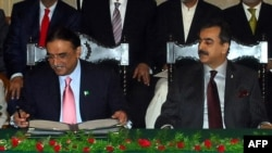 Pakistani President Asif Ali Zardari (left) signing a constitutional reform law as Prime Minister Yousuf Raza Gilani (R) looks on during a ceremony in Islamabad in April 2010.