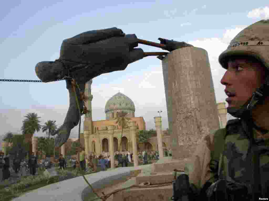 U.S. Marine Corp Assaultman Kirk Dalrymple watches as a statue of Iraq's President Saddam Hussein falls in central Baghdad April 9, 2003. U.S. troops pulled down a 20-foot (six meters) high statue of President Saddam Hussein in central Baghdad on Wednesday and Iraqis danced on it in contempt for the man who ruled them with an iron grip for 24 years. In scenes reminiscent of the fall of the Berlin Wall in 1989, Iraqis earlier took a sledgehammer to the marble plinth under the statue of Saddam. Youths had placed a noose around the statue's neck and attached the rope to a U.S. armoured recovery vehicle. REUTERS/Goran Tomasevic