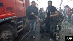 Жители пригорода Хомса несут раненного при взрыве машины человека к спасателям. 9 апреля 2014 года.