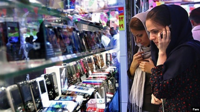 A woman talks on her mobile phone as she browses for mobile phones in Tehran. (file photo)