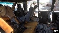 Жарылыстан бүлінген көлік қаңқасының жанында тұрған адам. 13 наурыз 2014 жыл. (Көрнекі сурет)
