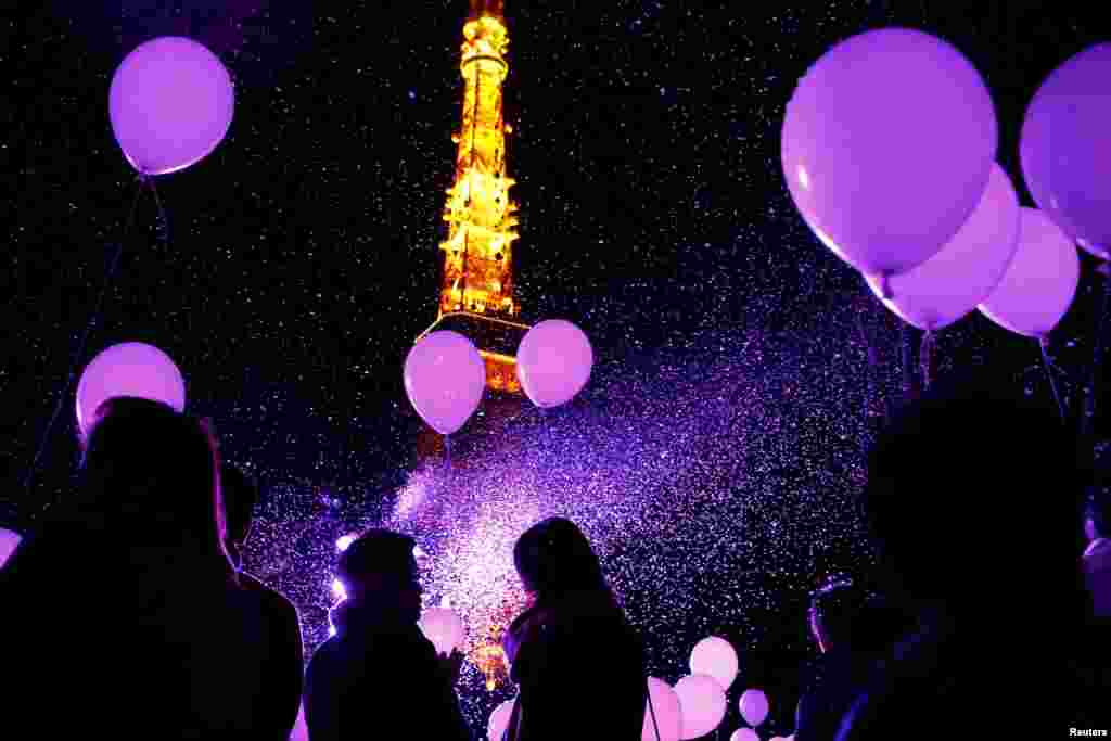 People hold balloons to release them at the turn of the New Year at a hotel in front of the landmark Tokyo Tower in Tokyo, Japan, on December 31. (Reuters/Thomas Peter)