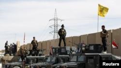 جنود عراقيون يقفون فوق مركبات عسكرية في تكريت - 27 آذار 2015