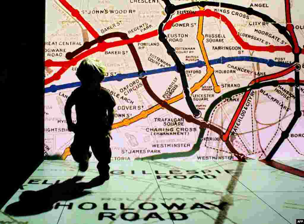 A young visitor to the London Transport Museum runs in front of an old Underground map.