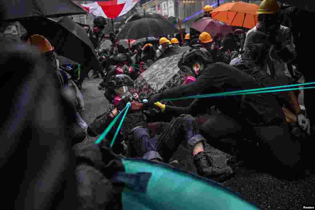 Протестующие используют рогатки против спецназа, Гонконг, 25 августа 2019 года.