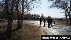 Женщины и дети идут по дороге в селе Садовое, смотрят на то, как ограждается их село противопаводковыми насыпями.