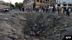 Afghan security forces and residents stand near the crater left by a deadly truck-bomb attack in Kabul on May 31.