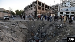 Afghan security forces and residents stand near the crater left by a truck bomb attack in Kabul on May 31.