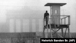 Когда стена была совсем юной. Житель Западного Берлина смотрит с наблюдательной вышки на восточную часть города у Бранднебургских ворот. Ноябрь 1961 года