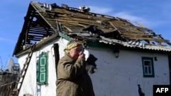 Gündogar Ukrainada Debalsewe regionyndaky Nikişynede ýerleşýän ýumrulan jaýyň öňünde garry ene öz göz ýaşyny süpürýär.